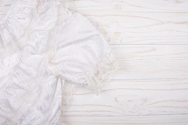 Primo piano di una comunione o di un vestito da sposa bianca su un fondo di legno