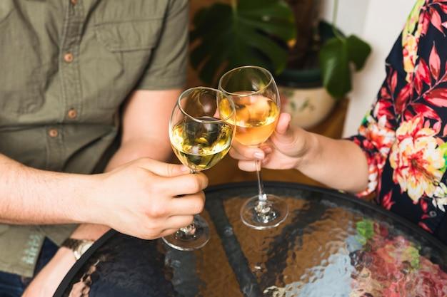 Primo piano di una coppia che tosta i bicchieri di vino