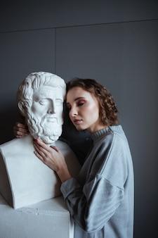 Primo piano di una donna appoggiata su un busto di marmo