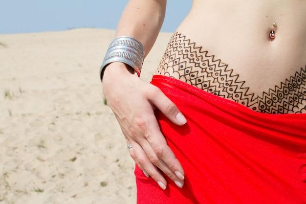 Primo piano di una donna bianca con un tatuaggio mehendi sulla parte inferiore dell'addome con un velo rosso, nel deserto