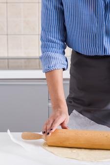 Primo piano di una donna che appiattisce la pasta con il matterello