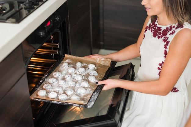 Primo piano di una donna che dispone il vassoio dei biscotti in forno