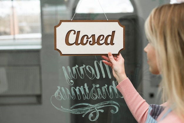 Primo piano di una donna che esamina l'etichetta chiusa che appende su un vetro della stanza frontale di negozio