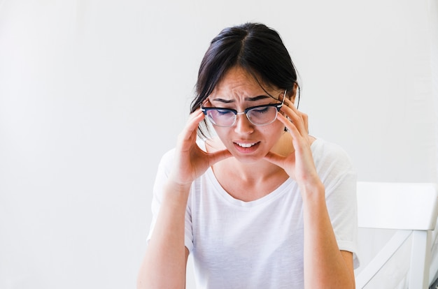 Primo piano di una donna che ha dolore severo nell'emicrania isolata sul contesto bianco