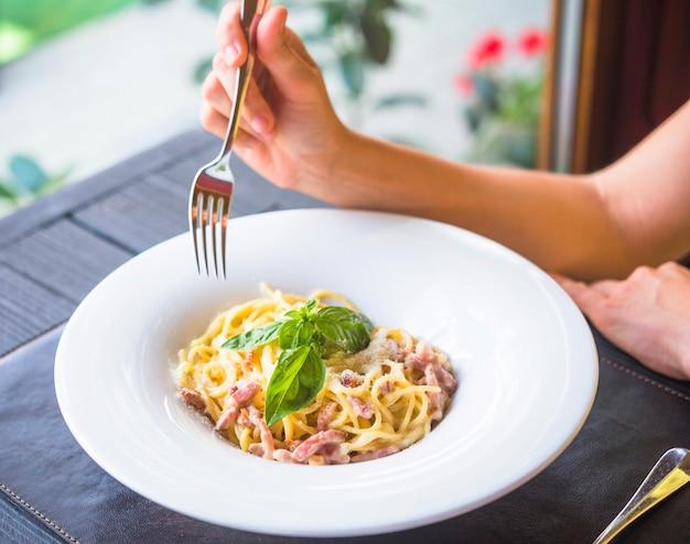 Primo piano di una donna che mangia gli spaghetti con la forchetta