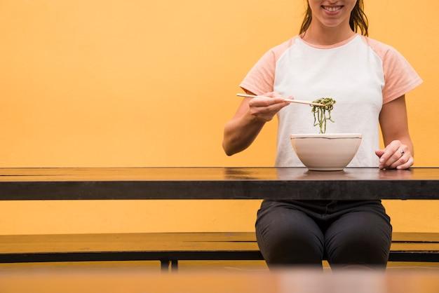 Primo piano di una donna che mangia le alghe verdi con le bacchette sulla tavola di legno contro il contesto giallo