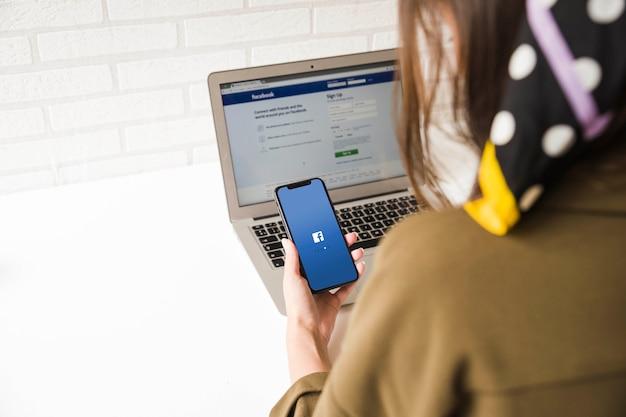 Primo piano di una donna che prova ad accedere all'applicazione di facebook sul cellulare e sul computer portatile