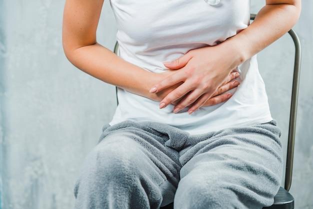 Primo piano di una donna che si siede sulla sedia che ha mal di stomaco