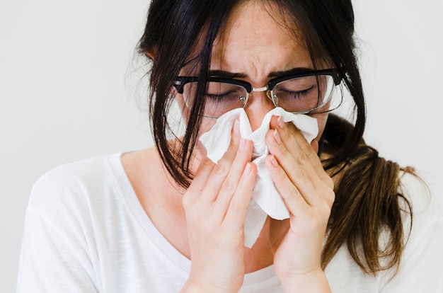 Primo piano di una donna che soffia il naso in carta velina contro sfondo bianco