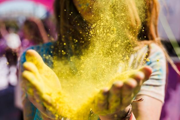 Primo piano di una donna che spolvera il colore giallo di holi