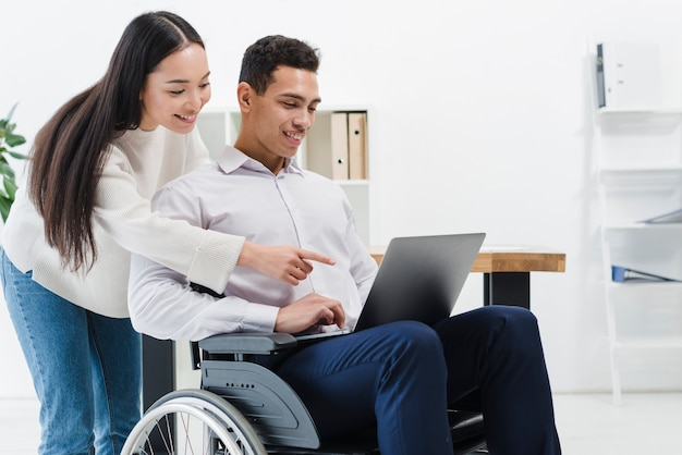 Primo piano di una donna che sta dietro l'uomo d'affari che si siede sulla sedia a rotelle che mostra qualcosa sul computer portatile