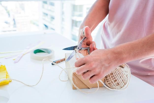 Primo piano di una donna che taglia il filo dalla bobina con le forbici sulla tavola bianca