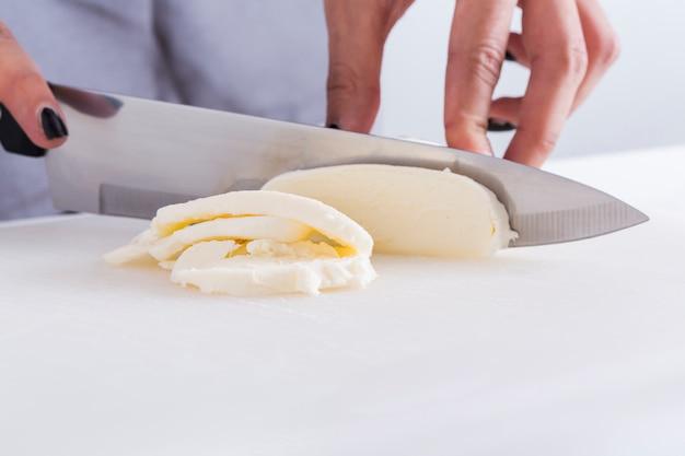Primo piano di una donna che taglia il formaggio con il coltello sulla tavola bianca