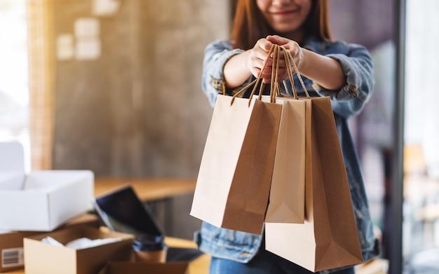 Primo piano di una donna che tiene e che mostra i sacchetti della spesa con il pc della compressa e la scatola postale del pacchetto sulla tavola per il concetto online di acquisto