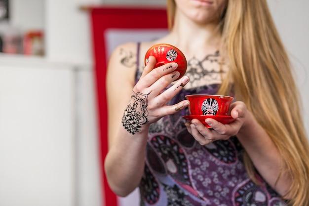 Primo piano di una donna che tiene il tè cinese in una cerimonia del tè tradizionale