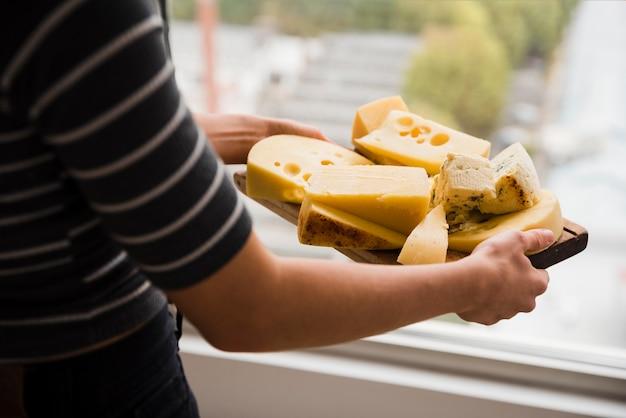 Primo piano di una donna che tiene tagliere di legno con fette di formaggio
