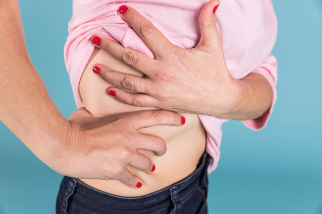 Primo piano di una donna con dolore nella parte bassa della schiena