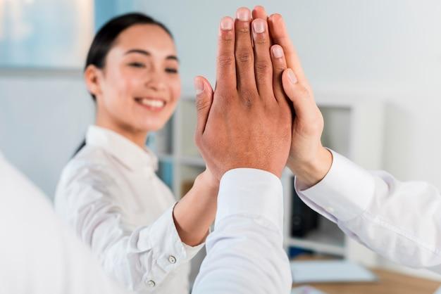 Primo piano di una donna d'affari dando il cinque contro i suoi soci in affari