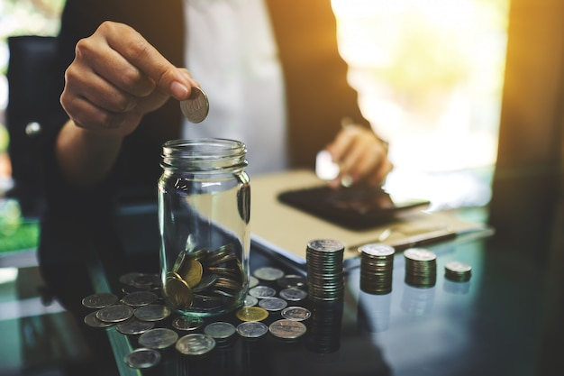Primo piano di una donna di affari che mette le monete in un barattolo di vetro, calcolando e impilando soldi per il risparmio e il concetto finanziario