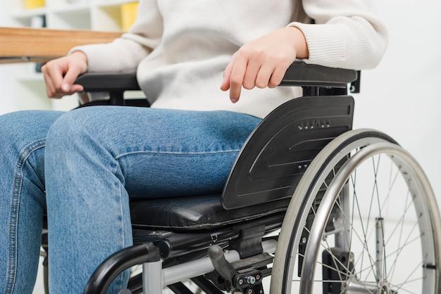 Primo piano di una donna disabile che si siede sulla sedia a rotelle