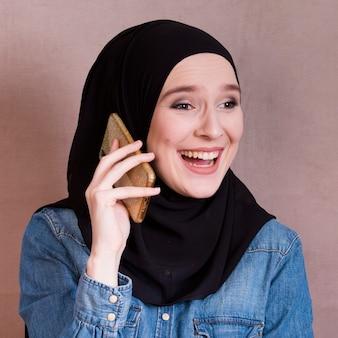 Primo piano di una donna eccitata parlando sul cellulare