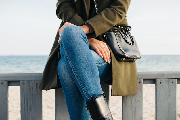 Primo piano di una donna in un cappotto verde e jeans