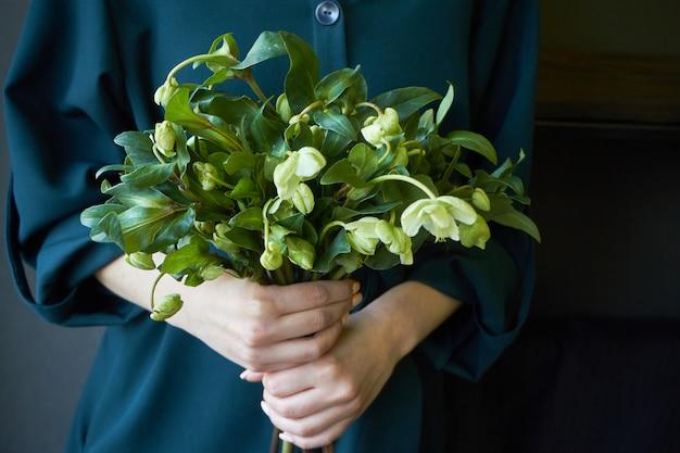 Primo piano di una donna in un vestito verde che tiene un mazzo dei fiori di fioritura freschi dell'elleboro, fuoco selettivo