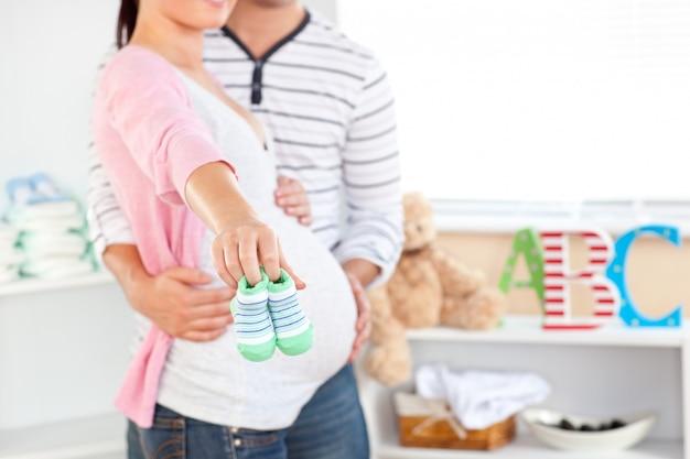 Primo piano di una donna incinta luminosa che tiene i pattini di bambino mentre marito che tocca la sua pancia nella stanza del loro bambino futuro