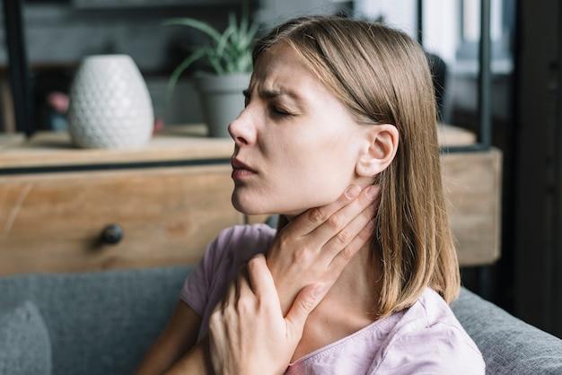 Primo piano di una donna nel dolore che ha mal di gola