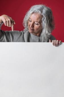 Primo piano di una donna senior che punta al cartellone bianco nero su superficie rossa