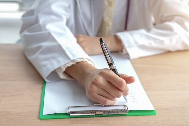 Primo piano di una dottoressa seduta su una nota