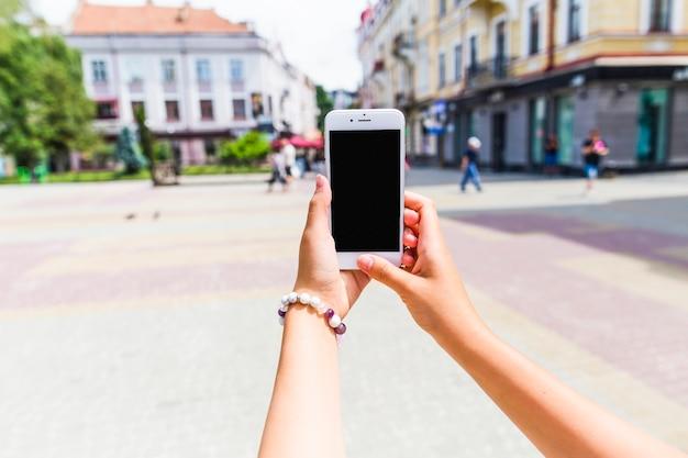 Primo piano di una femmina di scattare una foto della strada urbana attraverso il cellulare