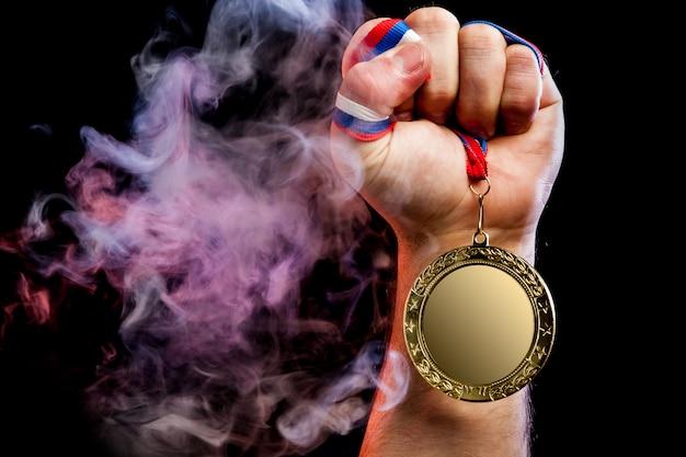 Primo piano di una forte mano maschile in possesso di una medaglia d'oro per un risultato sportivo