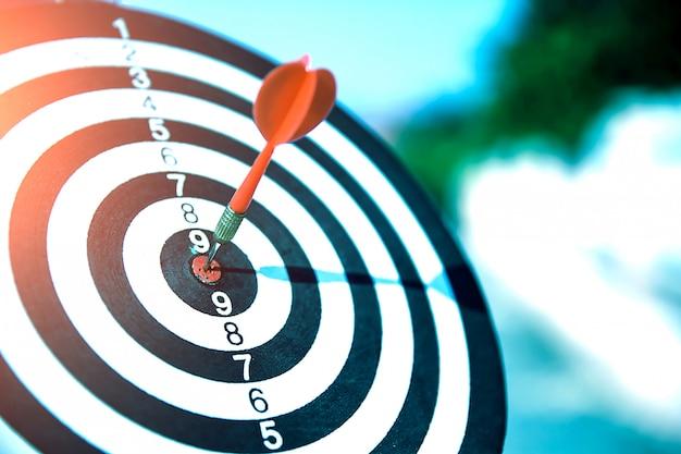 Primo piano di una freccia di colore rosso al centro di bullseye o occhio di bue per obiettivi aziendali e buon successo.