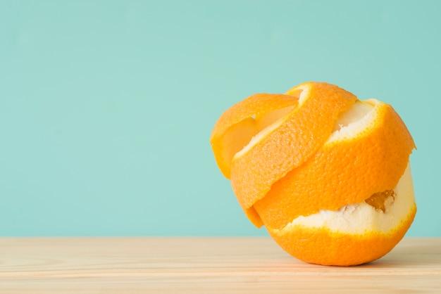 Primo piano di una frutta arancione sbucciata su superficie di legno