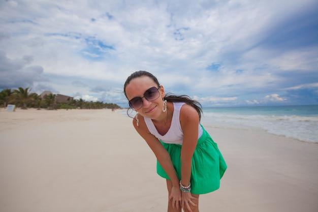 Primo piano di una giovane bella donna sulla spiaggia esotica bianca