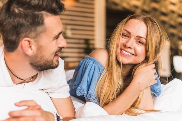 Primo piano di una giovane coppia felice sdraiata sul letto