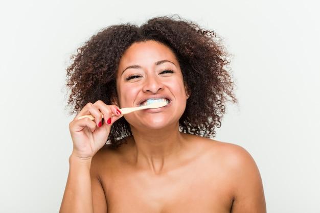 Primo piano di una giovane donna afro-americana a lavarsi i denti con uno spazzolino da denti