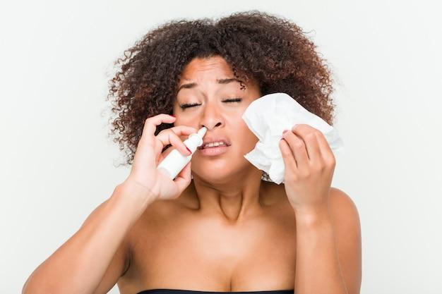 Primo piano di una giovane donna afro-americana con uno spray nasale