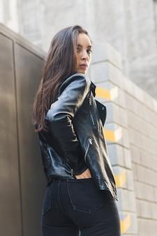 Primo piano di una giovane donna alla moda con la mano nella tasca posteriore dei jeans