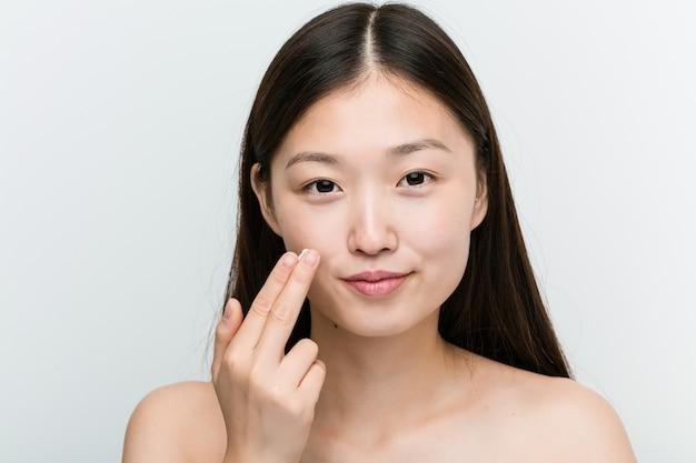 Primo piano di una giovane donna asiatica bella e naturale, applicare una crema idratante