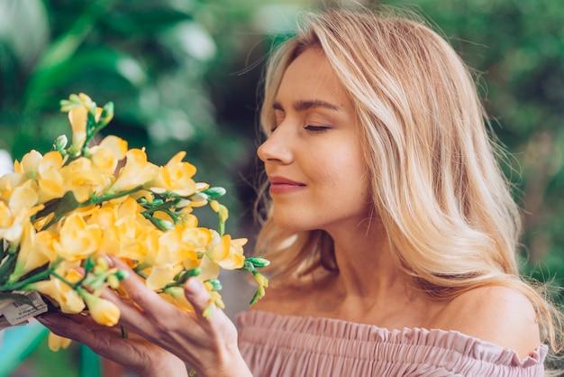 Primo piano di una giovane donna bionda che odora i fiori di fresia