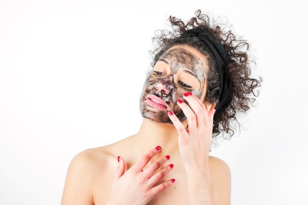 Primo piano di una giovane donna che applica maschera nera su sfondo bianco