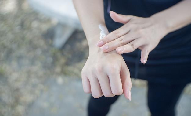 Primo piano di una giovane donna che applica protezione solare al suo braccio.