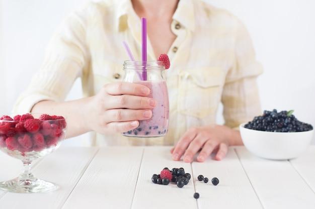 Primo piano di una giovane donna che beve un frullato
