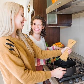 Primo piano di una giovane donna che cucina gli spaghetti nella casseruola con la sua amica