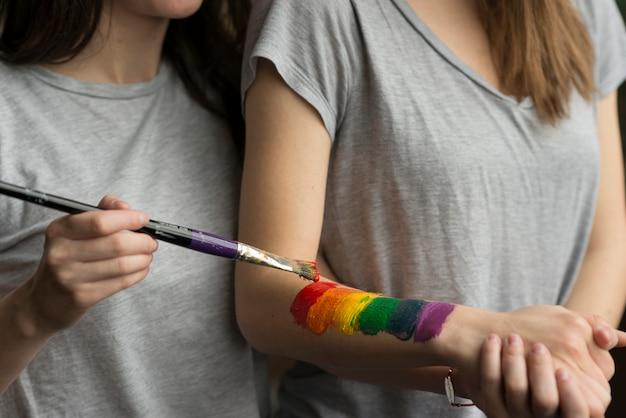 Primo piano di una giovane donna che dipinge la bandiera lbgt sulla mano della sua ragazza con il pennello