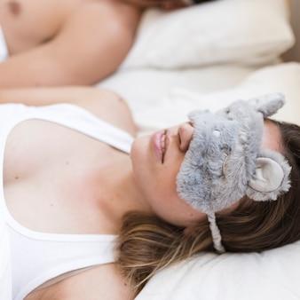 Primo piano di una giovane donna che dorme sul letto con una maschera per gli occhi