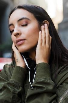 Primo piano di una giovane donna che gode della musica sul trasduttore auricolare