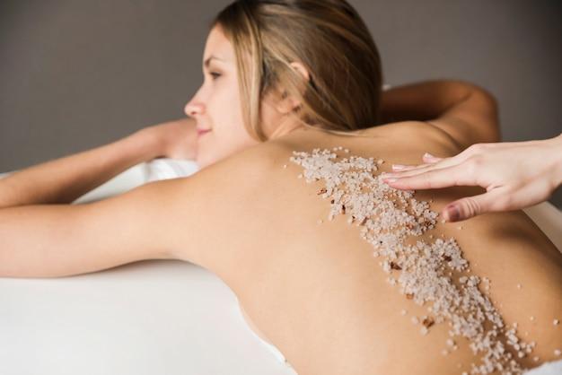 Primo piano di una giovane donna che ha trattamento esfoliante nella spa